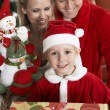 Cute Boy In Santa Claus Outfit Holding Gifts With Parents Behind — Stock Photo