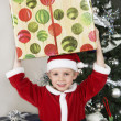 Boy In Santa Claus Outfit Carrying Present On Head - Stock Photo