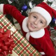 Boy In Santa Claus Outfit Holding Christmas Present - Stock Photo