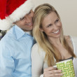 Man In Santa Hat Embracing Woman Holding Coffee Cup — Stock Photo #21951253