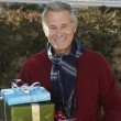 Senior Man Holding Gifts Outdoors - Stock Photo
