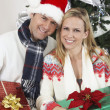 Couple Holding Gifts In Front Of Christmas Tree - Stock Photo