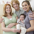 Stock Photo: Expectant Couple With WomAnd Baby By Cradle