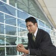 Stock Photo: BusinessmLeaning On Railing