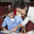 Stock Photo: Teacher Assisting Male Student In Classroom