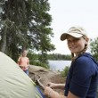 Teenage Girls Standing By Tent Near Lake — Stock Photo #21956255