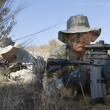 Soldiers Aiming Rifles In Field — Stock Photo