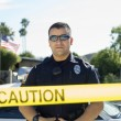 Police Officer Standing Behind Caution Tape — Stock Photo #21958119