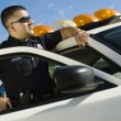 Stock Photo: Police Officer Leaning On Patrol Car