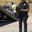 Police Officer Writing Notes At Car Crash Scene — Stock Photo