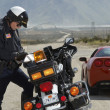 Traffic Cop Writing Against Motorcycle — Stock Photo #21958605