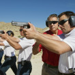Foto Stock: Instructor Assisting Officers With Hand Guns At Firing Range