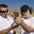 Foto Stock: Instructor Assisting WomWith Hand Gun