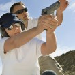 Stock Photo: Instructor Assisting WomWith Hand Gun At Firing Range