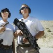 Stock Photo: MAnd WomHolding Guns At Firing Range