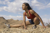 Female Jogger Stretching In Mountains — Stock Photo