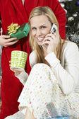 Kvinna använder mobiltelefon framför man håller julklapp — Stockfoto
