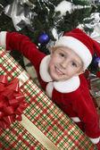 举行圣诞礼物的圣诞老人衣服的男孩 — 图库照片