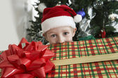 Boy In Santa Hat Peeking Over Gift Box — Stock Photo