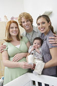 Expectant Couple With Woman And Baby By Cradle — Stock Photo