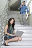Female Student Sitting While Man Walking Down Stairs — Stock Photo