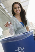 Female Student Throwing Plastic Bottle In Dustbin — Stock Photo