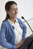Female Professor Standing In Front Of Podium — Stock Photo