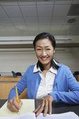 Kvinnliga professor anteckning ner anteckningar på papper — Stockfoto