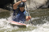 Young man whitewater kayaking — Stock Photo