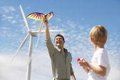 Pai e filho brincando com a pipa no parque eólico — Foto Stock