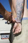 Officer Handcuffing Tattooed Young Man — Stock Photo