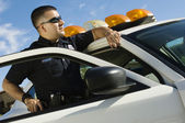 Police Officer Leaning On Patrol Car — Stock Photo