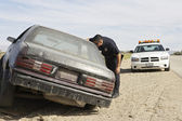 Police Officer Looking Into Abandoned Car — Stock Photo