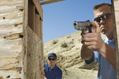 Man Watching Colleague Aiming Hand Gun — Stock Photo
