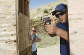 Two Men Aiming Hand Guns At Firing Range — Stock Photo