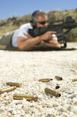 Bullets On Ground With Man Aiming Machine Gun — Stock Photo