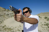 Man Aiming Hand Gun At Firing Range In Desert — Stock Photo
