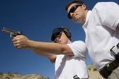 Instructor Assisting Woman With Hand Gun At Firing Range — Stock Photo