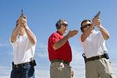 Instructor ayudando a hombres con armas de mano en tiro — Foto de Stock