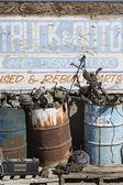 Teken en roestige vaten in autokerkhof — Stockfoto