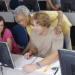 Stock Photo: Senior Teacher Assisting Students
