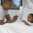 Father Checking Daughter's Temperature In Bed — Stock Photo #21962745