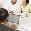 Financial Advisor Using Laptop With Couple In Discussion Over Documents — Stock Photo #21963859