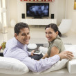 Couple With Remote Control Sitting On Sofa — Стоковая фотография