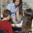 Teacher Helping Students In Classroom - Stock Photo