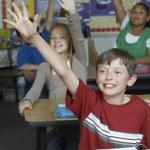 elever att höja händerna i klassrummet — Stockfoto