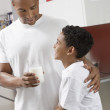 Man Giving Glass Of Milk To Son — Stock Photo #21969289