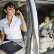 Business Woman Using Mobile Phone With Son In Car — Stock Photo #21969501