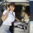 Businesswoman Using Cell Phone With Son Sitting In Car — Stock Photo #21969507