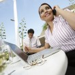 Businesswoman On Call With Colleague In Background — Stock Photo